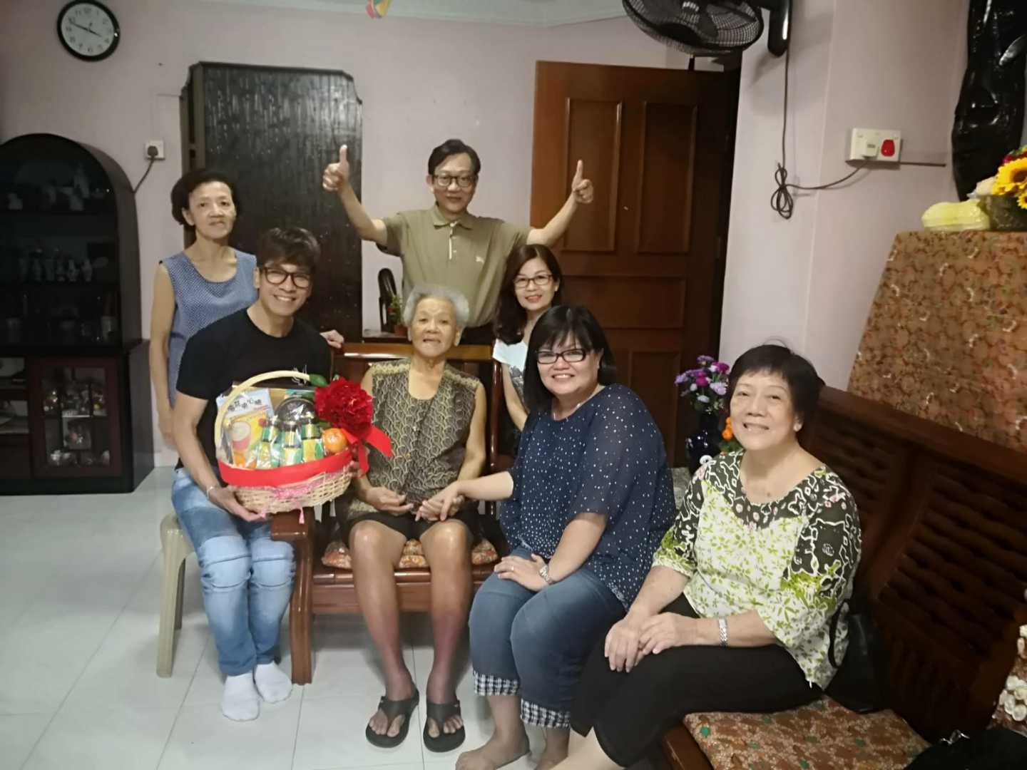 Reverend Joey Tan (seated left), and his ministry team delivering a Chinese New Year hamper to a church member who hasn't been able to come to church due to health reasons. Photo courtesy of Grace AOG.