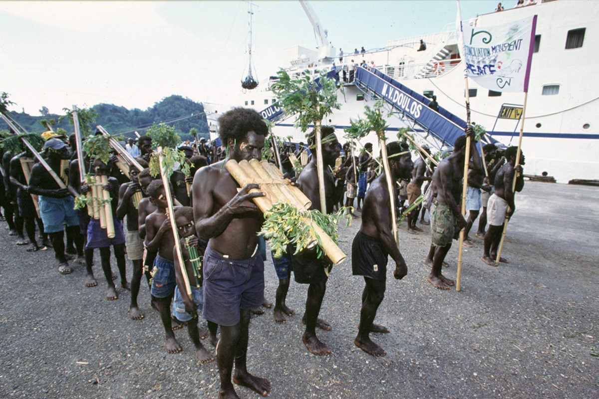 Doulos' leaders among local people playing traditional instruments as they mark the reconciliation ceremony in Bougainville with a procession on the quayside (By Tom Brouwer, OM)