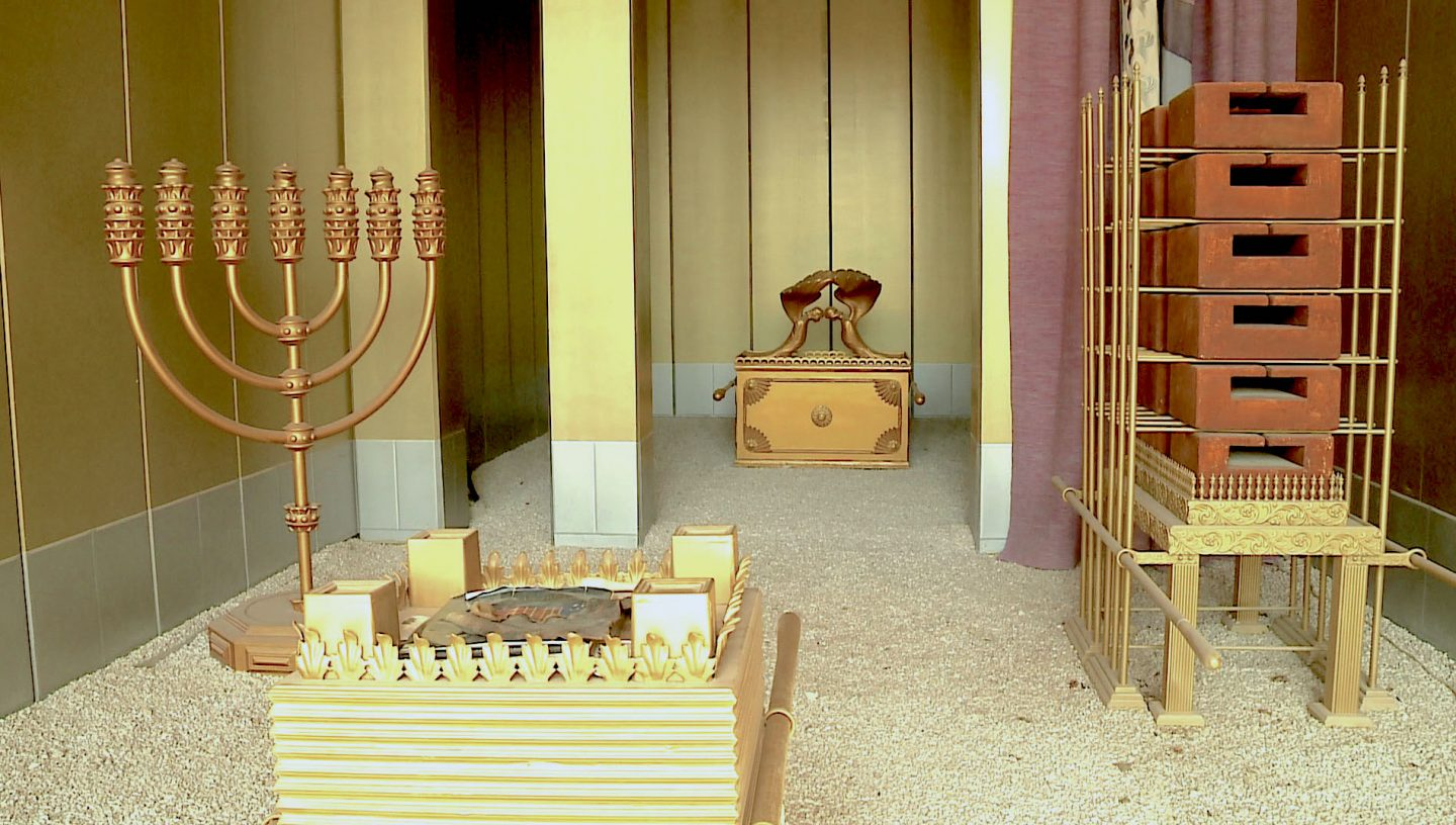 An exhibit of a life-sized replica of the Tabernacle in Ariel, Israel. Here, the menorah (leftmost item) has its place in the Tent of Meeting along with the Ark of the Covenant and the Table of Showbread. Photo from Eshel Hashomron Hotel, Israel.