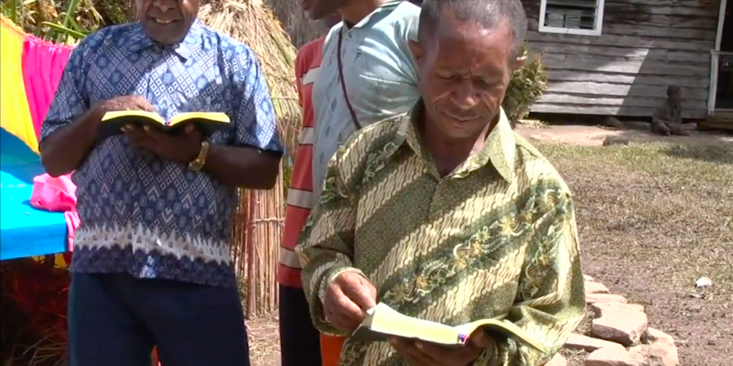 The Kimyal tribe from West Papua, Indonesia, holding a copy of the first New Testament in their language, as depicted in Imagine Life without the Bible. Screengrab from Imagine Life without the Bible.